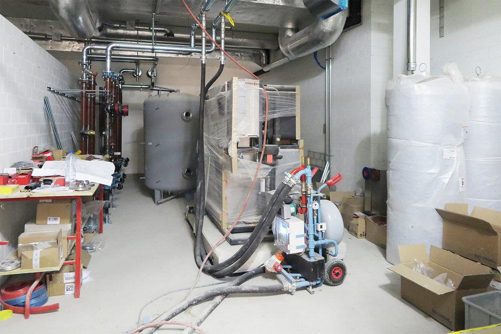Heizverteiler, Speicher und Kältemaschine (noch eingepackt) im 1. UG. Provisorische Übergabestation Bauheizung im vorderen Bereich.