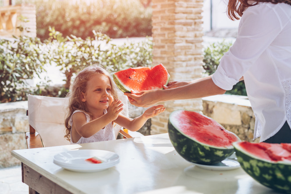 mother-giving-child-watermelon.jpg