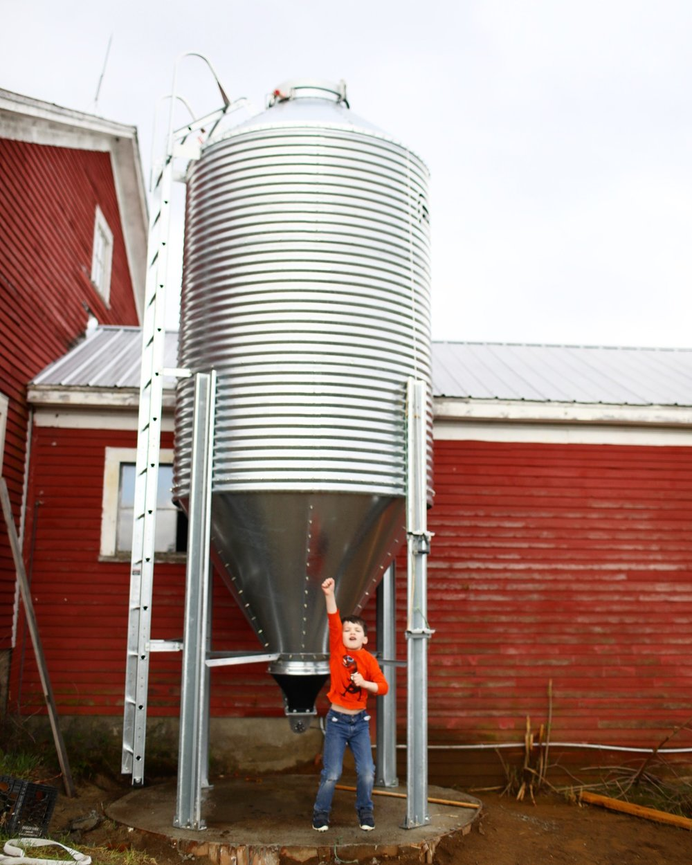 Hank {age 6} jumping for joy with the new Brock silo! {While it was being built, all the kids pretended it was a spaceship and spent endless hours inside...and also put to work tightening some bolts!}