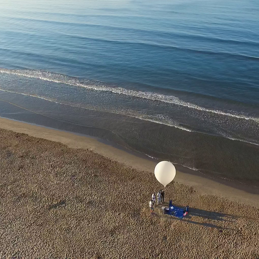 Drone image of a Near Space high altitude balloon being inflated on a sandy beach