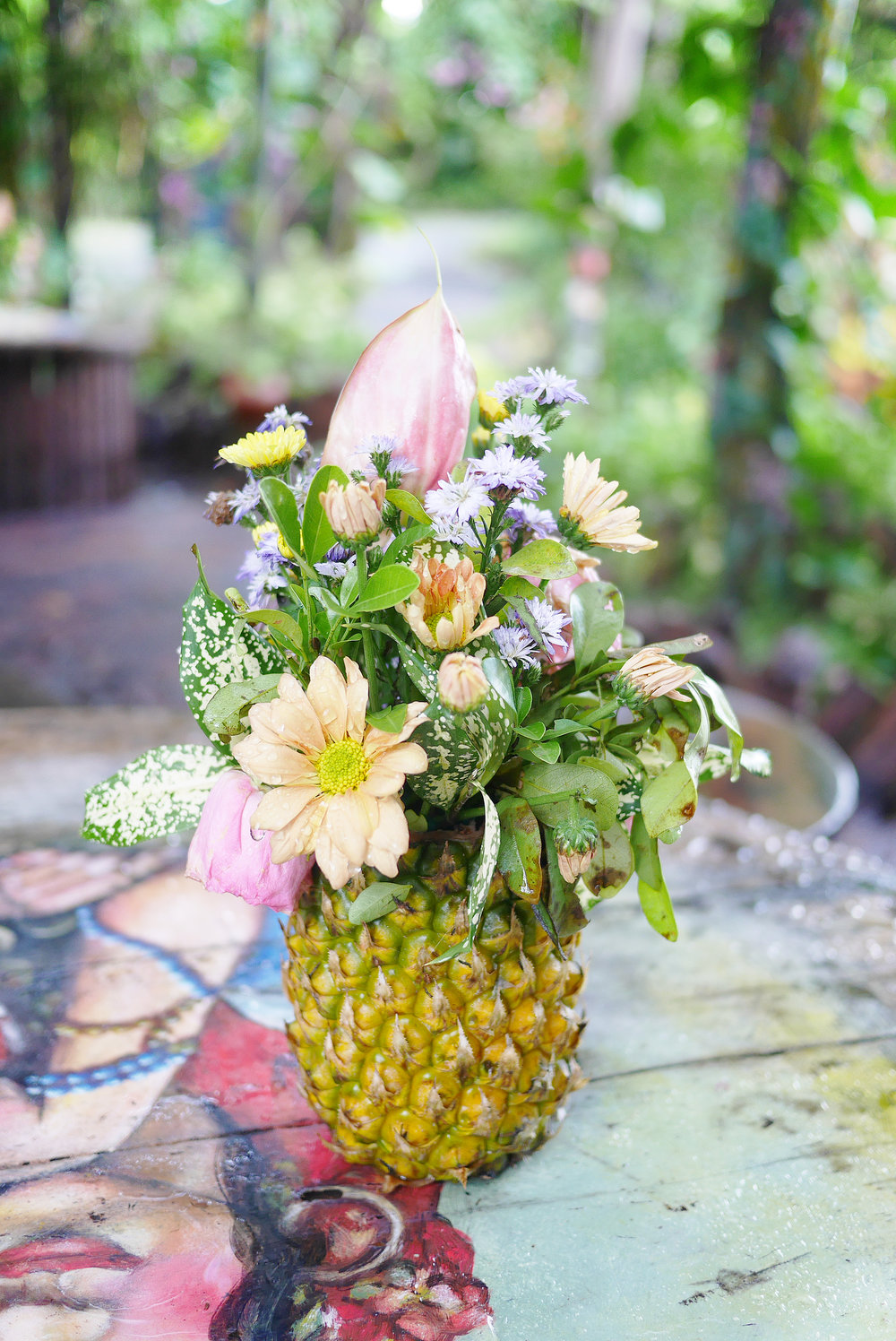 Adorable pineapple with fresh flowers on top for the table centerpiece