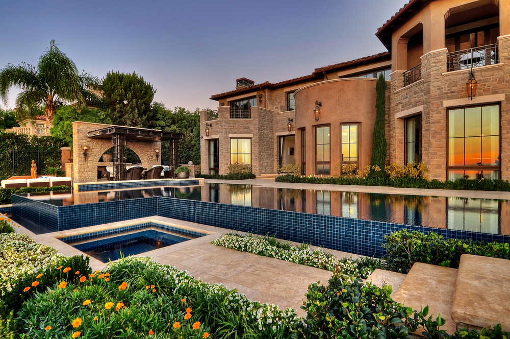 swimming pool and patio with statues and hot tub at Newport Harbor, California home