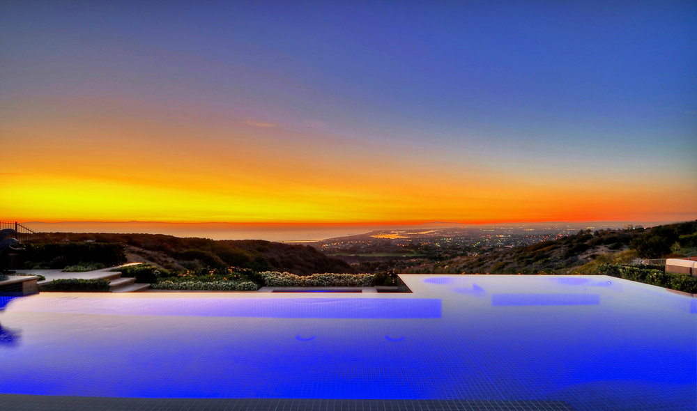 Negative edge swimming pool and patio with statues and hot tub at Newport Harbor, California home