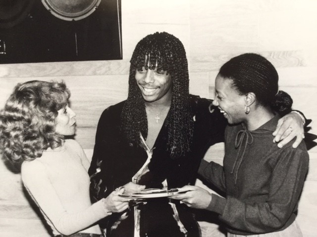 "In 1982, Rick James hands over the tape of the Temptations' ""Standing On The Top,"" which he wrote and produced, to Motown's Raynoma Singleton (left) and Brenda Boyce."