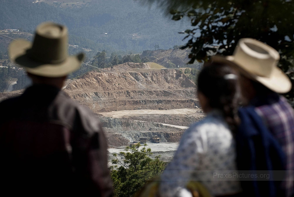 "OPEN PIT - The people of San Miguel Ixtahuacan, in Guatemala, look on at the steadily growing Marlin Mine. Open-pit mines are typically enlarged until either the mineral resource is exhausted, or until the operations are no longer profitable. Gold mining produces 79 tones of largely toxic waste for every ounce of gold. Many of the indigenous peoples living next to these mines struggle to comprehend the point of it all. ""Who came up with the idea that gold should be worth so much anyway?"" asks Alejandro, ""it's only a yellow stone that shines! Life should be more valuable than gold."""
