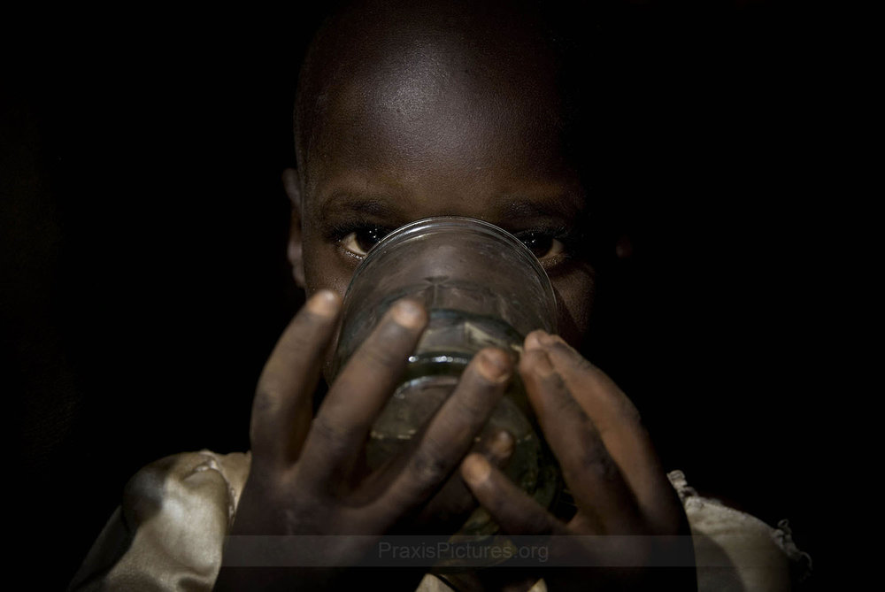 "NYAKABALE - Mabibhi's granddaughter, in Nyakabale, Tanzania, is pictured here drinking the water that residents believe has been contaminated by the nearby Geita Gold Mine. Residents report that the water now tastes bitter and smells foul. Human rights lawyer Tundu Lissu argues that  ""the description of the deaths and other health problems reported by the villagers of Nyakabale are consistent with the symptoms associated with cyanide poisoning."""
