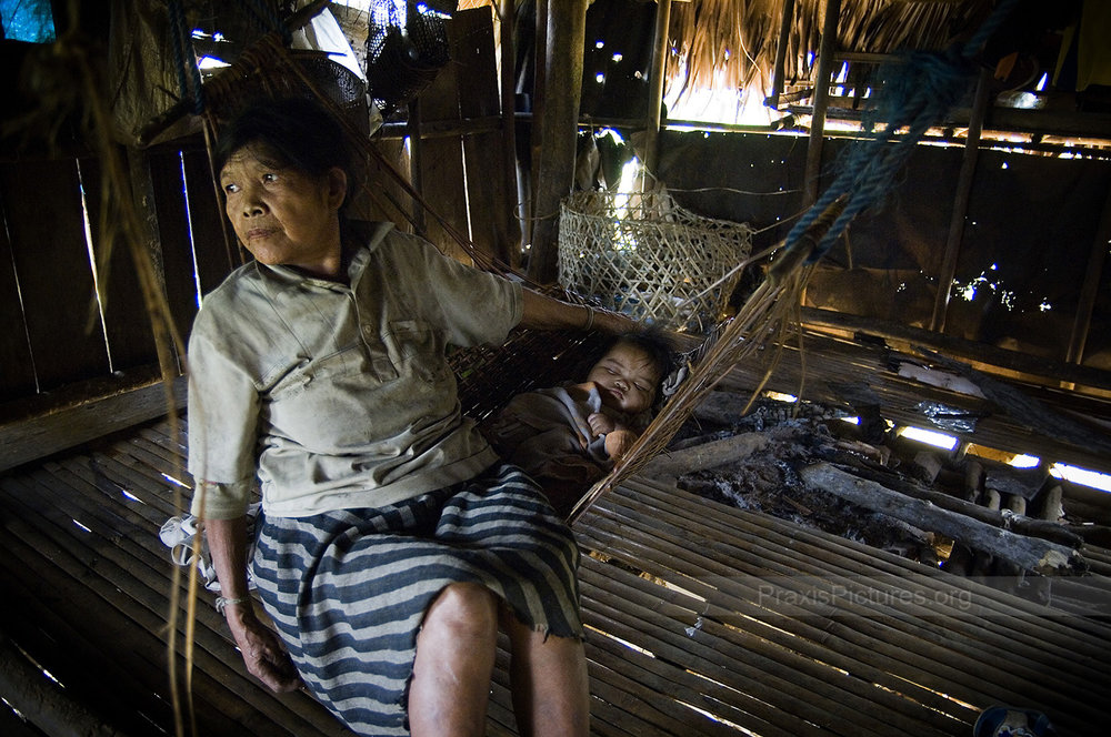 LUNINGNING - Luningning rests in a hammock with her granddaughter in the village of Kisluyan, on the Philippine island of Mindoro. The Alangan are one of 8 indigenous tribes in Mindoro, known collectively as the Mangyans. The Mangyans, who once occupied the whole island, are peaceful people who traditionally shy away from confrontation. As more and more settlers began moving to the island over the years, the Mangyans were gradually pushed higher and higher into the mountains. Now, with the proposed mine threatening to push them off what little land they have remaining, they are left with nowhere to go where they will be able to continue their traditional way of life. [This photo was shortlisted for  Verge Magazine's 2009 Travel with Purpose Photo of the Year ]