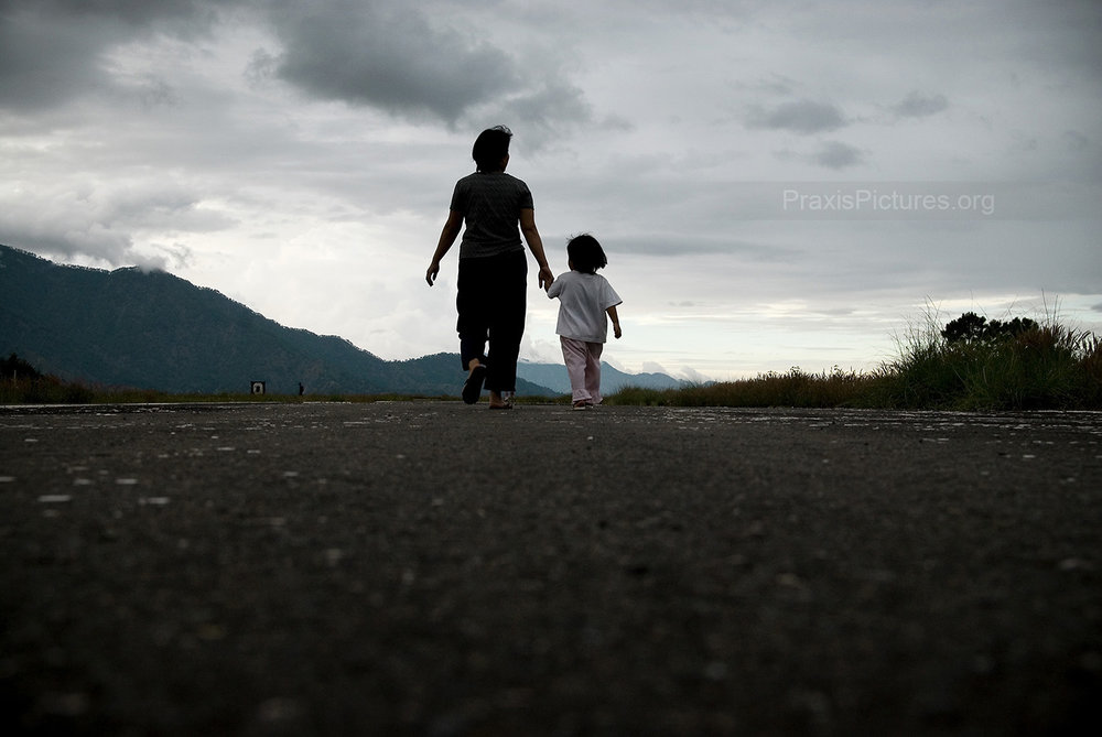 SOMEONE ELSE'S TREASURE - As the sun sets over the mountains of Benguet province, in the Philippines, Lilia and Trixie walk along the Victoria Gold Mine's airport runway near their home where all the gold is flown out of the province. The pattern has been repeated many times around the world; the companies come in promising to bring with them jobs, development and prosperity. In reality, the people who live there are not the ones benefiting from the wealth beneath their feet. For them, the social and environmental impacts will be felt for generations. Families are being torn apart, Indigenous cultures threatened, entire populations displaced, livelihoods lost, and ecosystems destroyed — all for someone else's treasure.