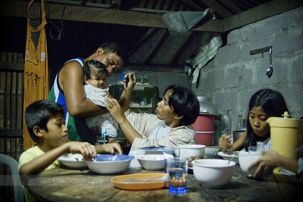 "FOOD SECURITY - Pili, Mindoro,  Henry  (second left) and his family enjoy a meal consisting of rice, fish and vegetables. The province of Oriental Mindoro is ranked third as the province which produces the most food in the Philippines, and is known as the ""food basket"" of the southern Luzon region.  The food security of Mindoro is under threat, however, by Crew Minerals' (now Intex Resources) proposed nickel mine. The proposed mine site is located within a critical watershed area that provides the irrigation for 70% of the province's vital rice fields and fruit plantations."