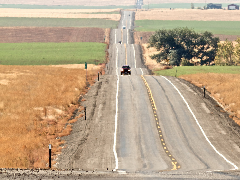 road-undulations-into-distance-with-cars-and-fields.png