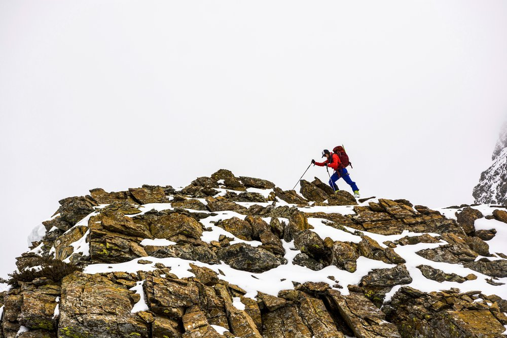 Steph walks to the edge of a rock outcropping on the Sheep's Head west ridge to peak over the side.