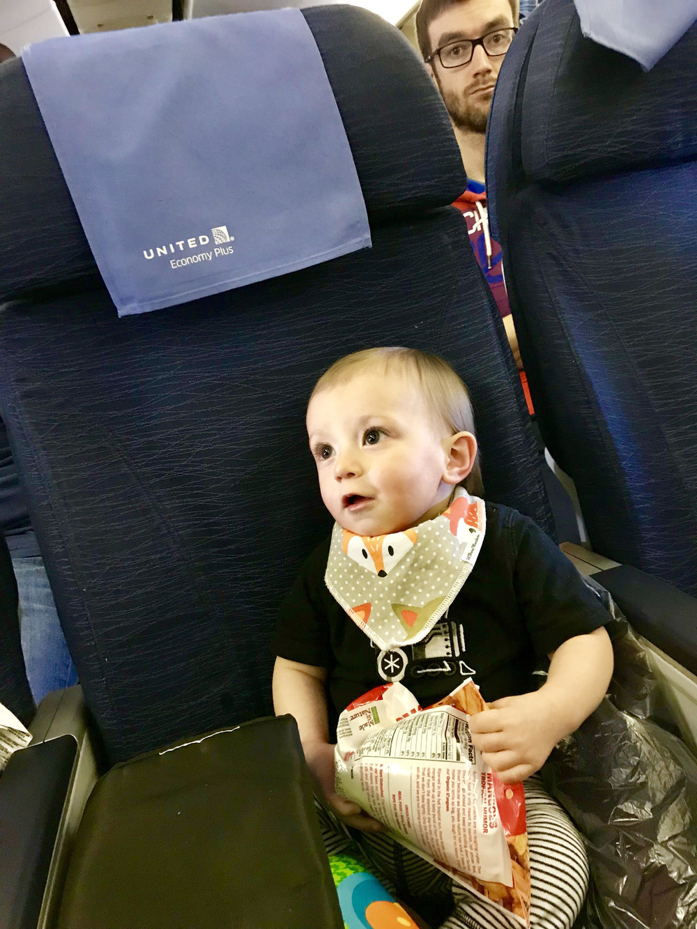 Preston is excited for his first flight overseas....and so is the guy sitting behind him.