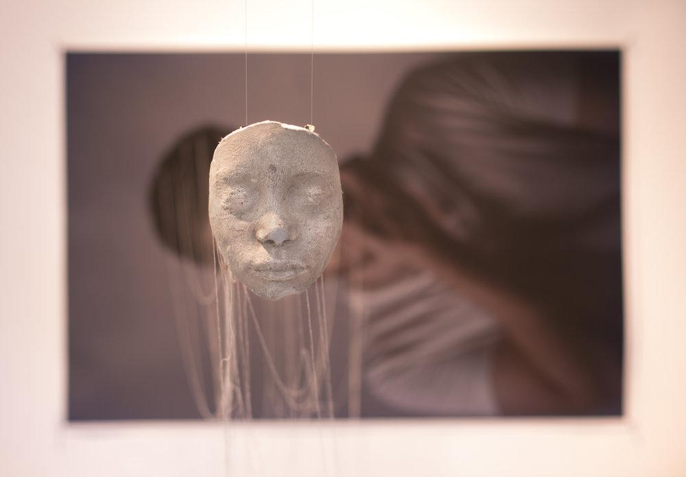 Confesión ,Rodrigo Dada,Instalación fotográfica y máscara de yeso,60 x 90 cm   Mi pieza trata sobre la máscara social y la identidad sexual, sobre cómo el ser humano se esconde tras capas de falsas identidades construidas para encajar en lo que la sociedad espera: máscaras que subsisten a través del tiempo, que dejan una marca y, aunque se desprenda, su fantasma perdura en el tiempo.  Mi pieza se relaciona con el laberinto como un homenaje a Vivencias / Máscaras.