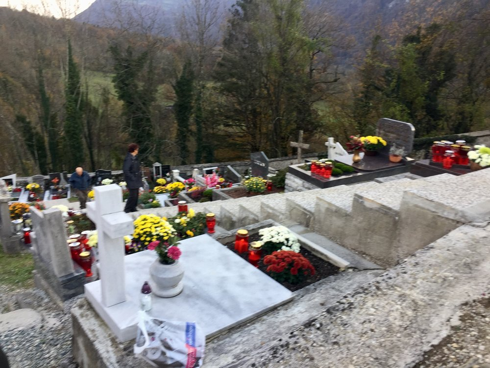 Families decorating graves on All Saints' Day