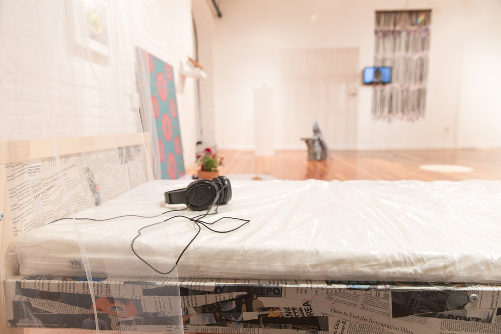 Simone Couto,   DREAMers,  2017, child's bed, mattress, headphones, moving blanket, newspaper with daca polices