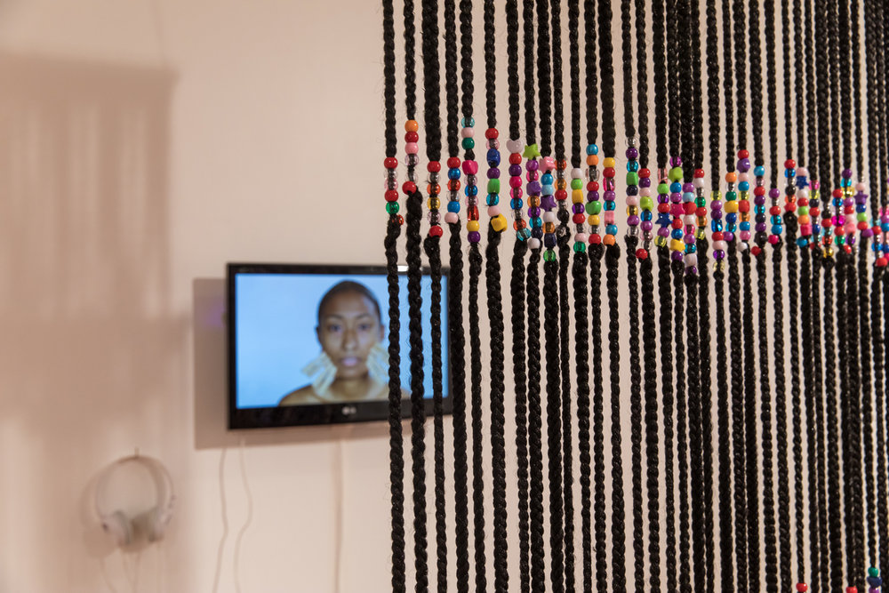 Dana Davenport,   Box Braid Curtain , 2016, synthetic kabkalon hair, beads;  Learning Korean, 2015,  video.