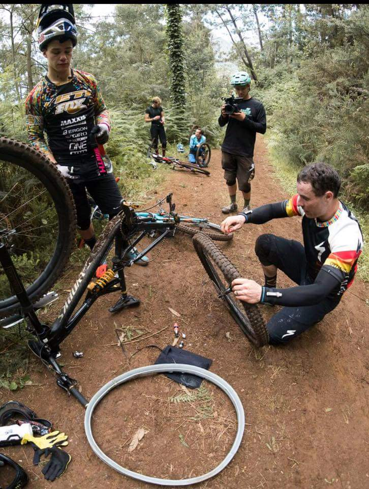 Jared Graves repairs a flat with help from Ritchie Rude.