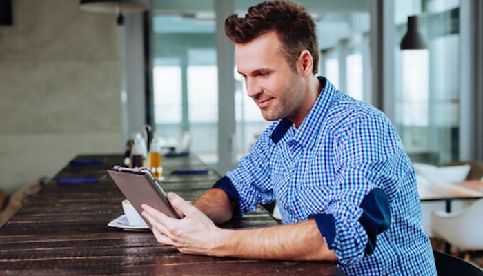Man-reading-tablet-at-wooden-table_Fotor.jpg