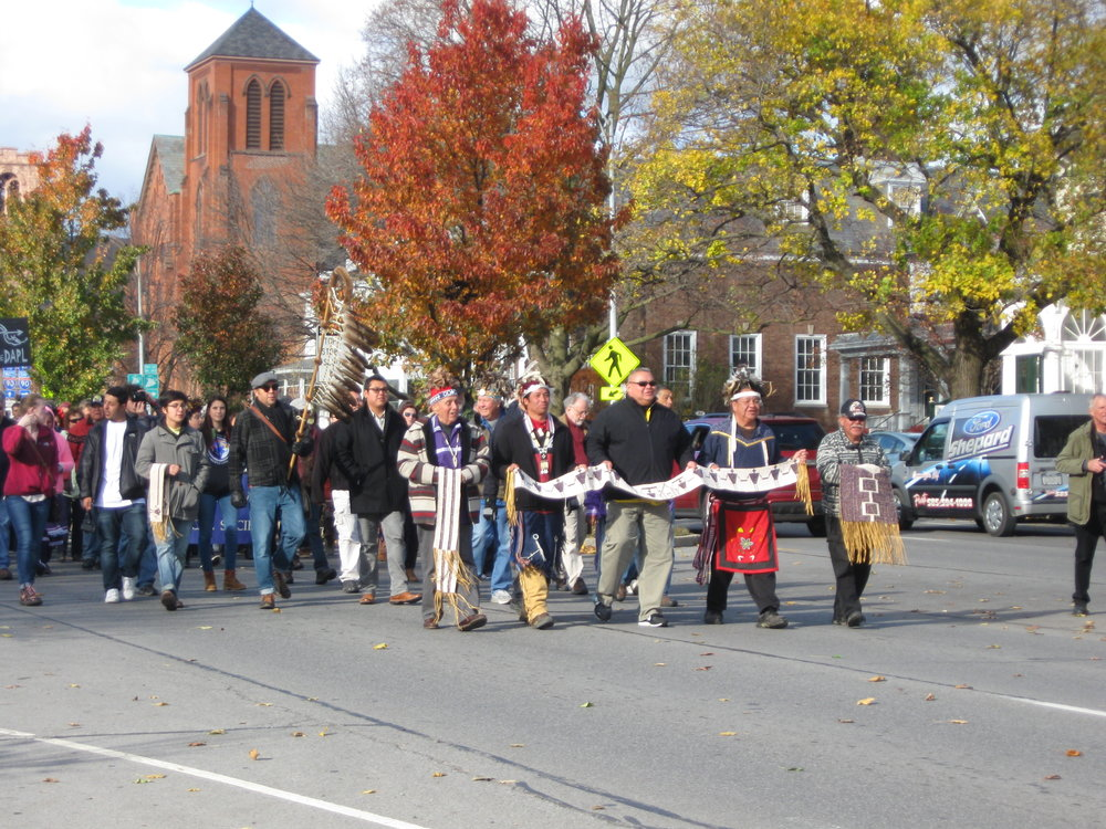 People of the Six Nations and allies walk up Main Street in Canandaigua toward the Ontario County Courthouse.