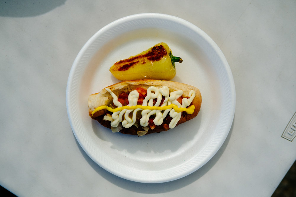 Sonoran dog: hot dog in a bolillo-style hot dog bun wrapped in bacon topped with pinto beans, onions, tomatoes, mayonnaise and mustard served roadside with a roasted spicy yellow pepper.