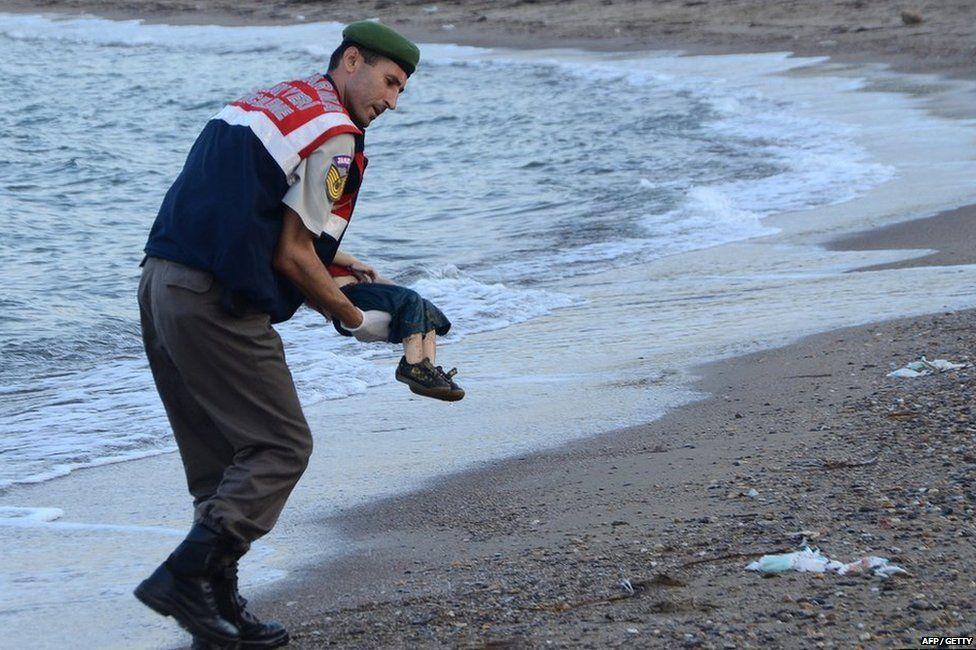Turkish police officer Mehmet Çıplak carries the body of Alan Kurdi. Photograph: AP