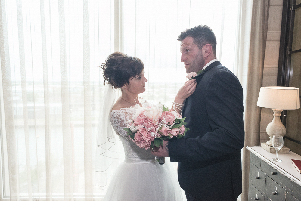 Bride fixes grooms tie next to window