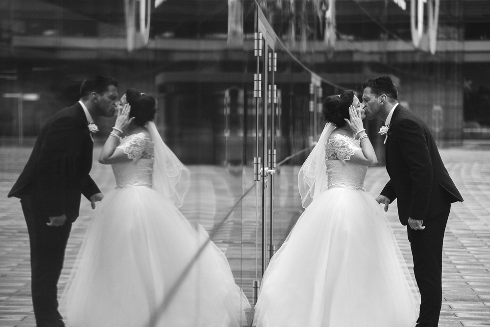 Bride and groom kiss in Media City with their reflection behind them