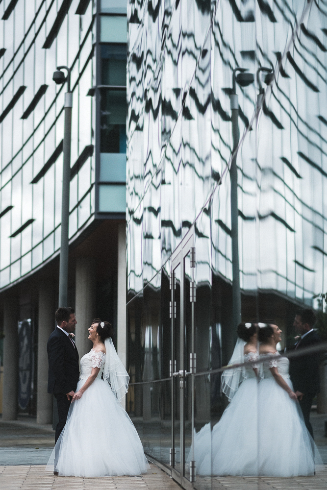 Bride and groom pose for photos with a reflection in Media City Salford Wedding