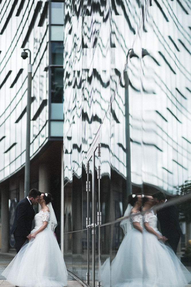 Bride and Groom pose for photos with reflections in a Media City, Salford Wedding