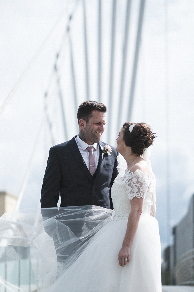 Bride and groom look lovingly at each other on Salford's Media City bridge