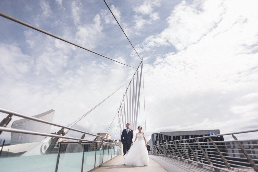 Bride and Groom pose on bridge in Salford's Media City. Wedding photography