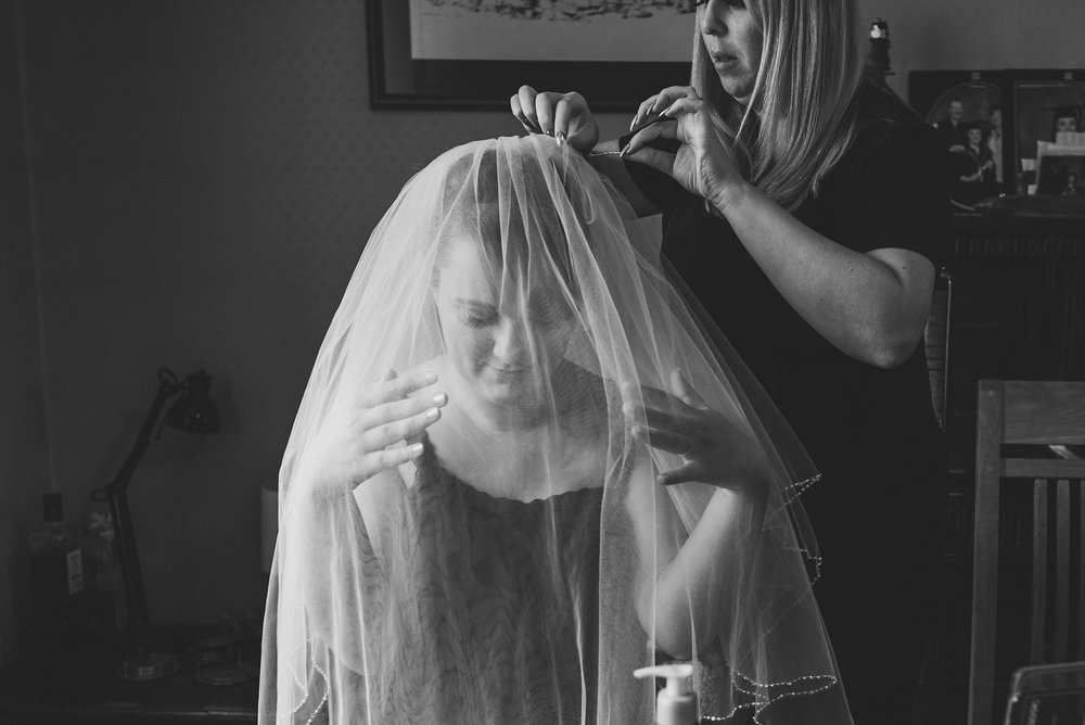Bride trying her veil on in the morning of her wedding