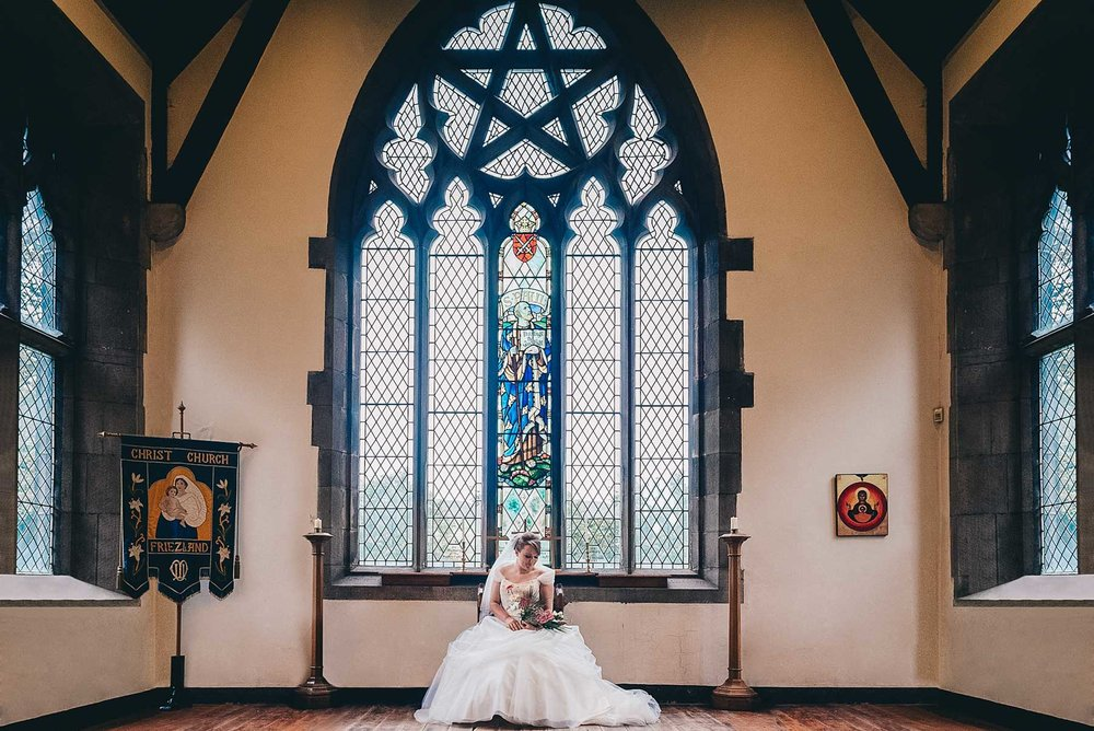 Bride looks down at flowers below grand church window