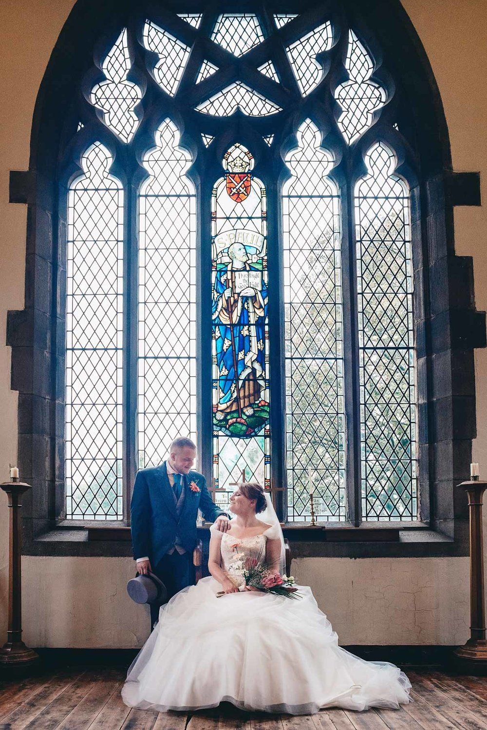 Bride and groom pose underneath window