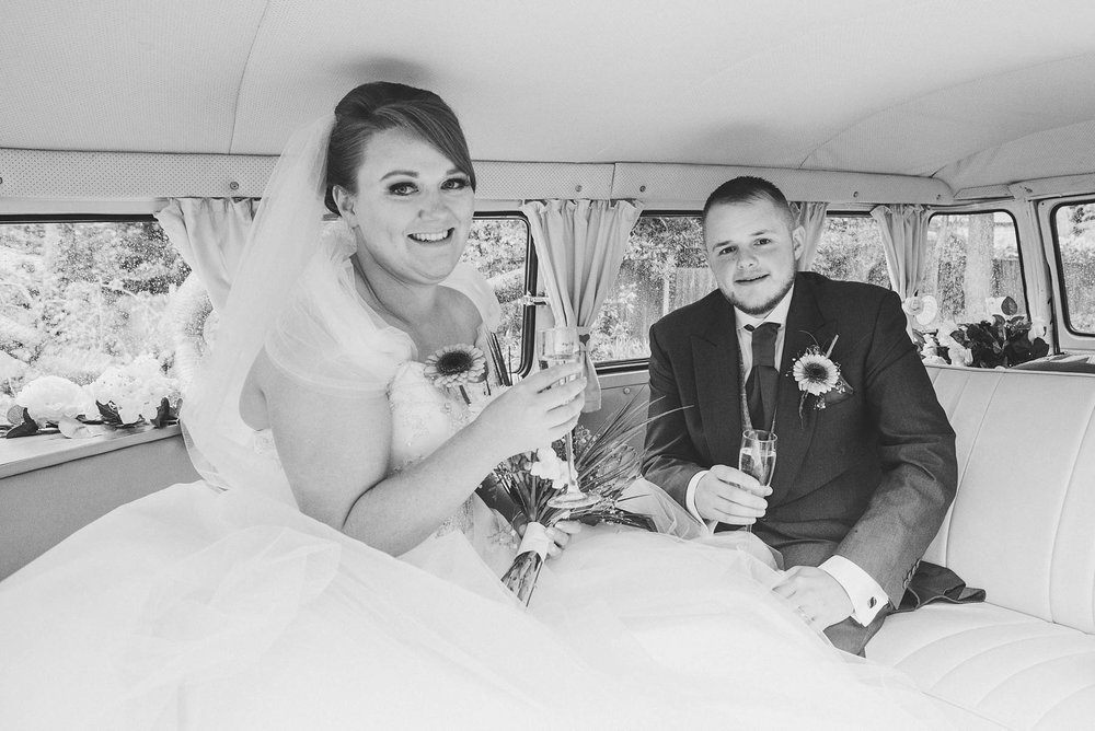 Bride and groom pose with drinks inside wedding campervan