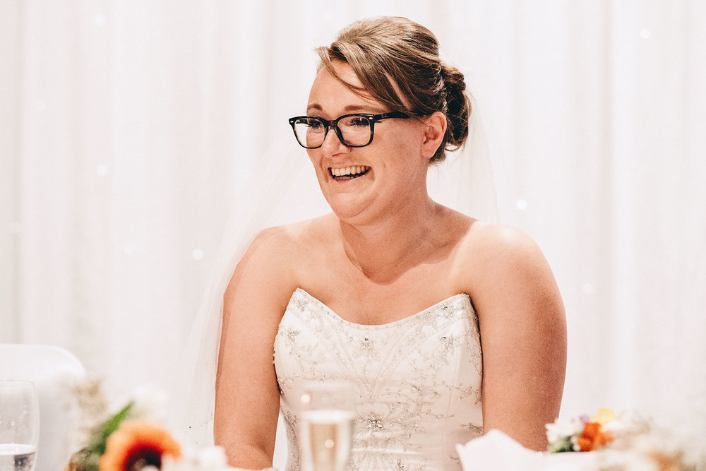 Bride laughs during wedding speeches