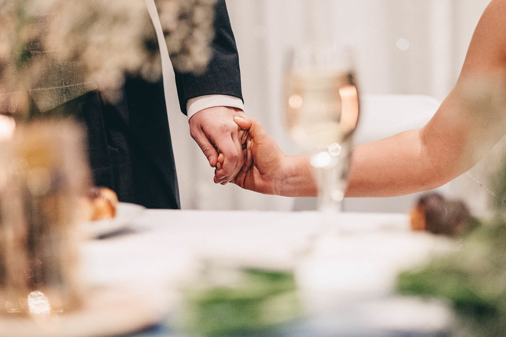 Bride and groom hold hands during speech