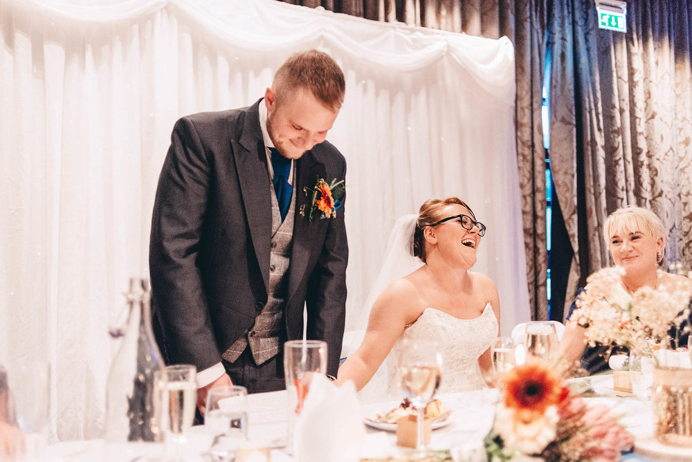 Bride laughs during speech given by groom