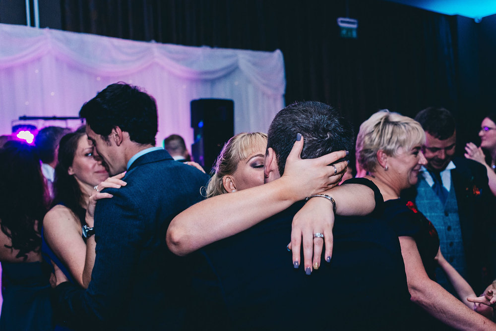 Woman kisses man on the dancefloor of wedding