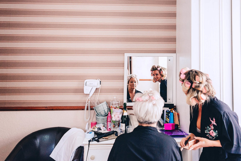 Bride looks in mirror during wedding prep