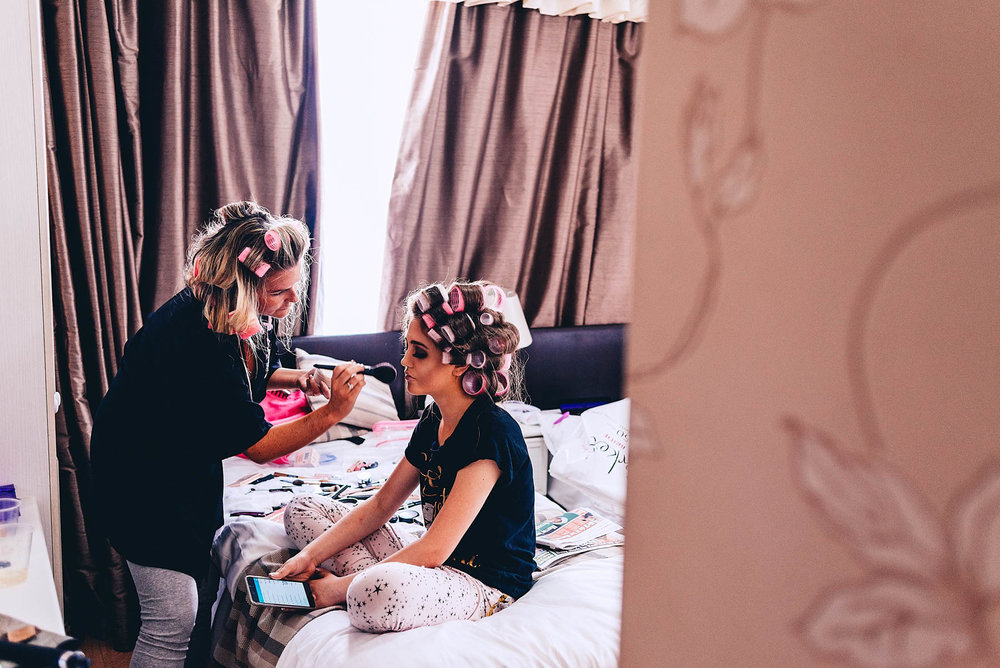 Bridesmaid getting makeup applied during wedding prep