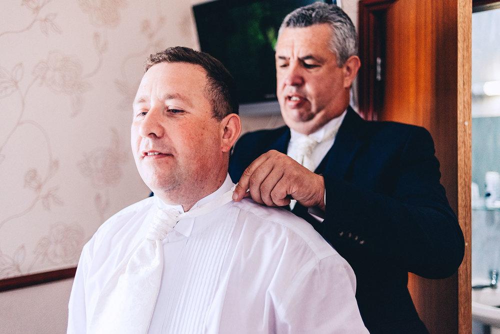 Best man tying grooms tie