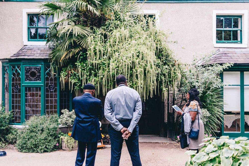 Three guests wait outside wedding venue