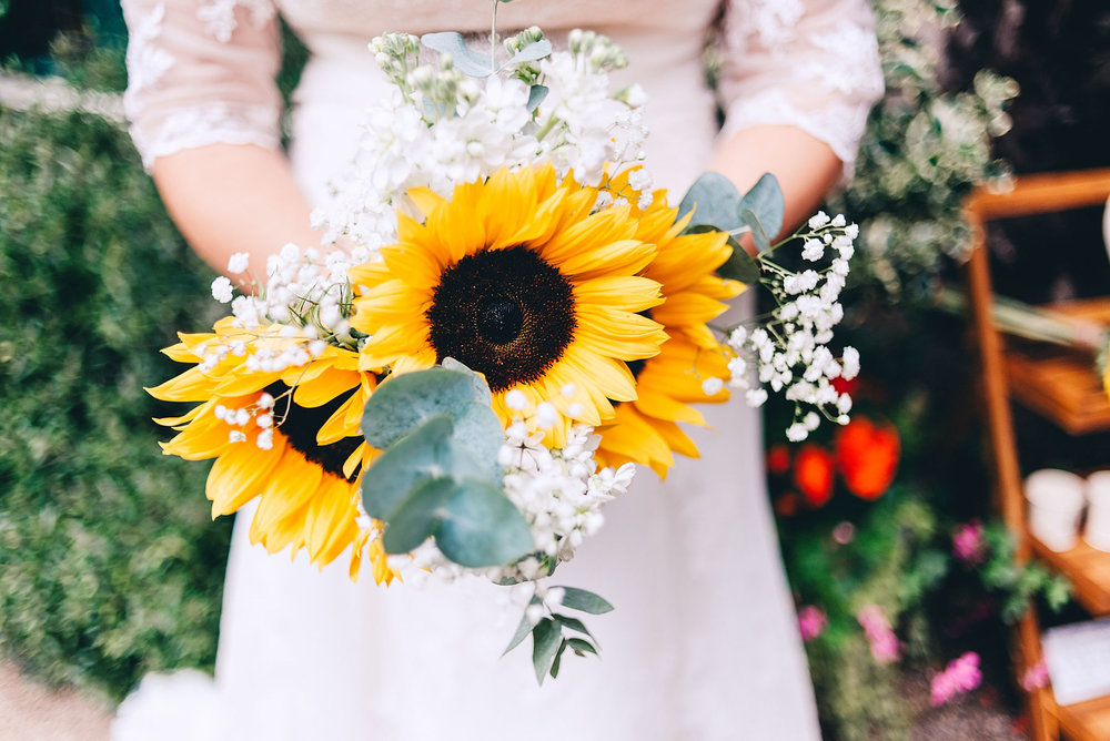 Bride holds a bouquet of sunflowers