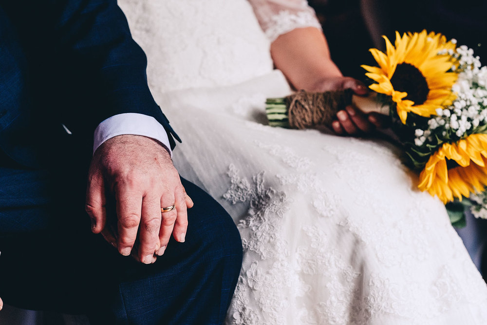 Groom holds bride's hand