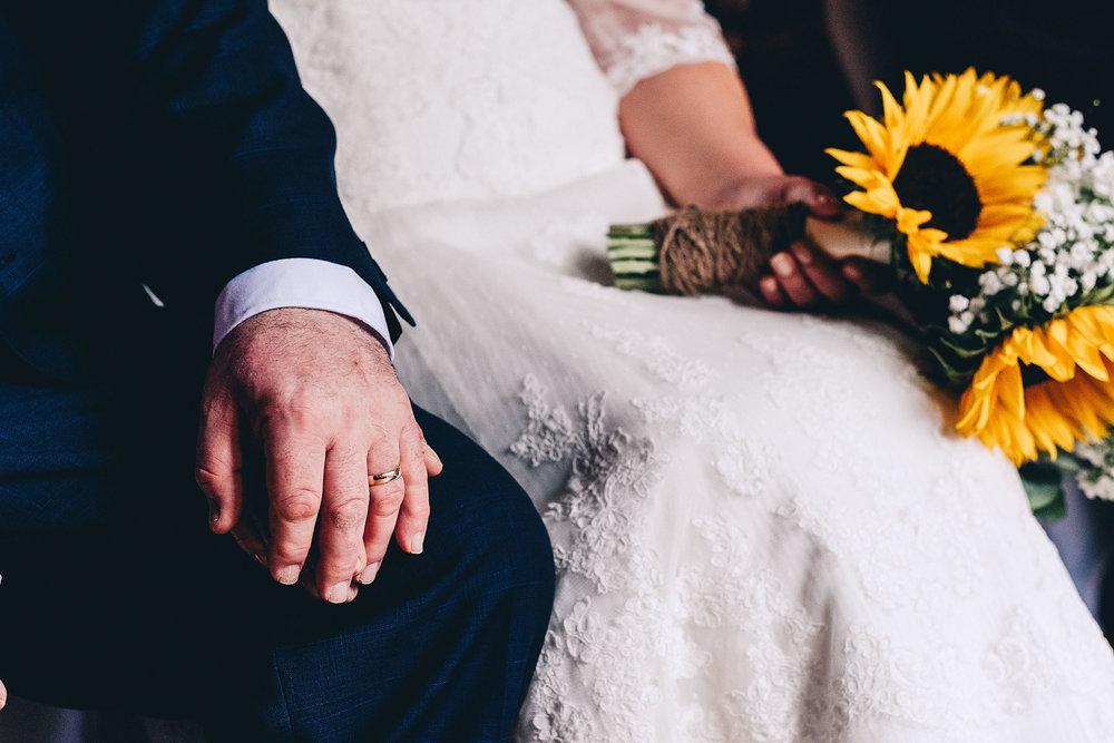 Groom holds bride's hand