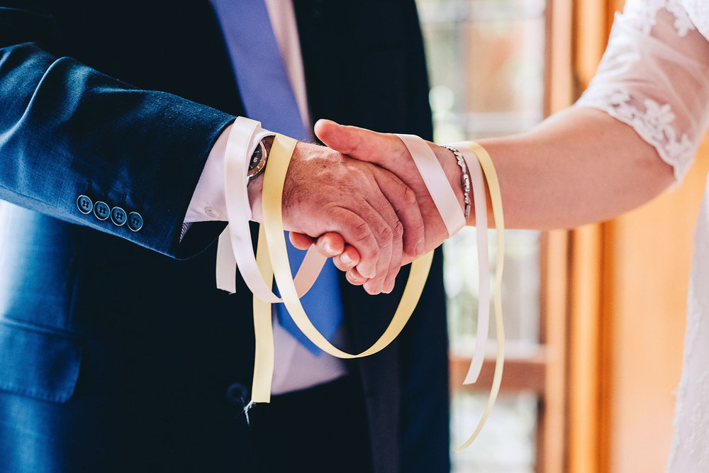 Handfasting ceremony close up of ribbons and hands