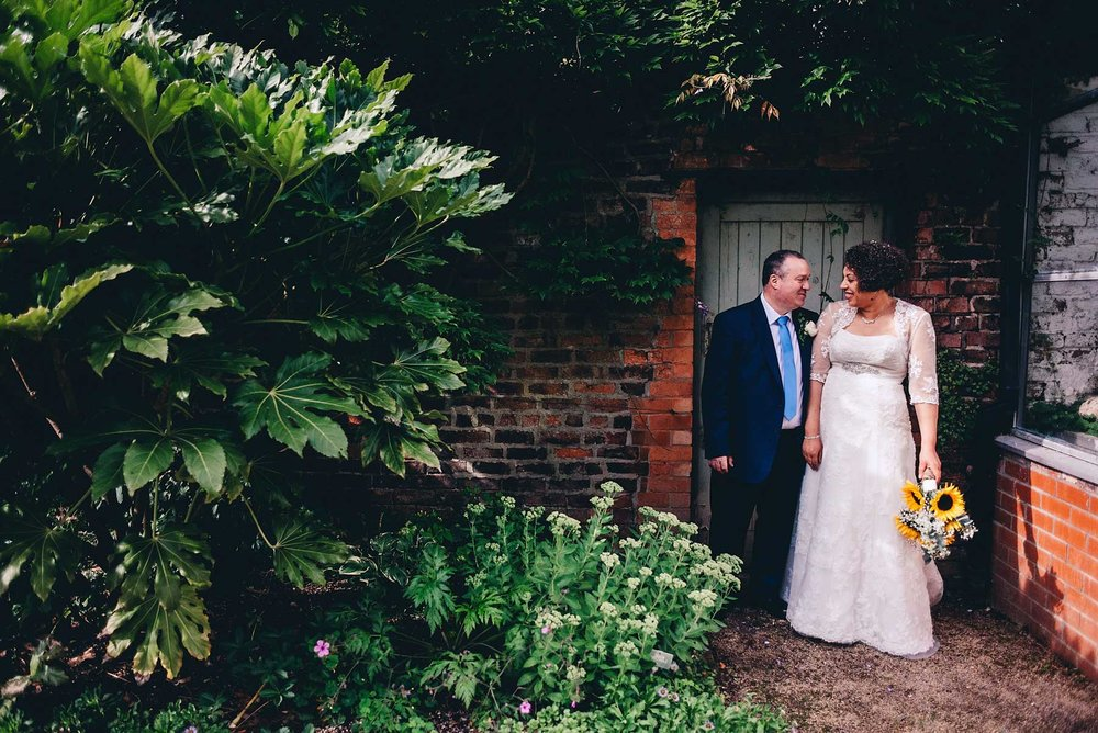 Bride and groom talk to each other in a garden