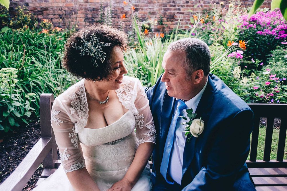 Bride and groom share a intimate moment sitting in a garden
