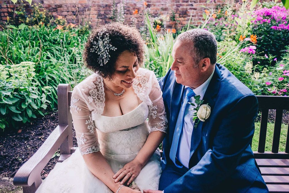 Bride and groom laugh while sitting in gardens